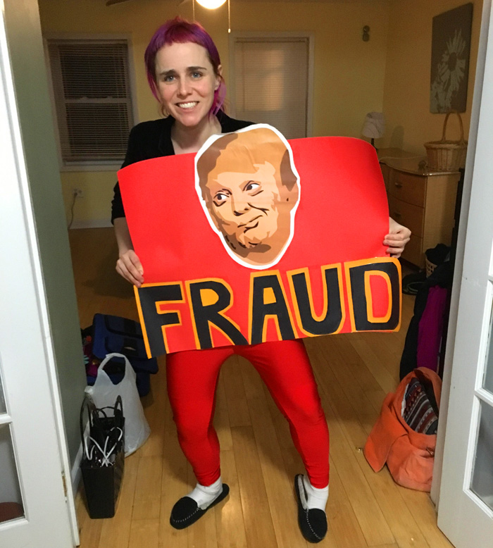 erica holding a sign with the face of Trmp and the word FRAUD