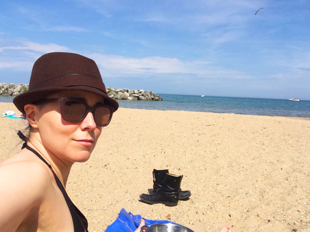 erica in sunglasses and German hat at the beach by Lake Michigan