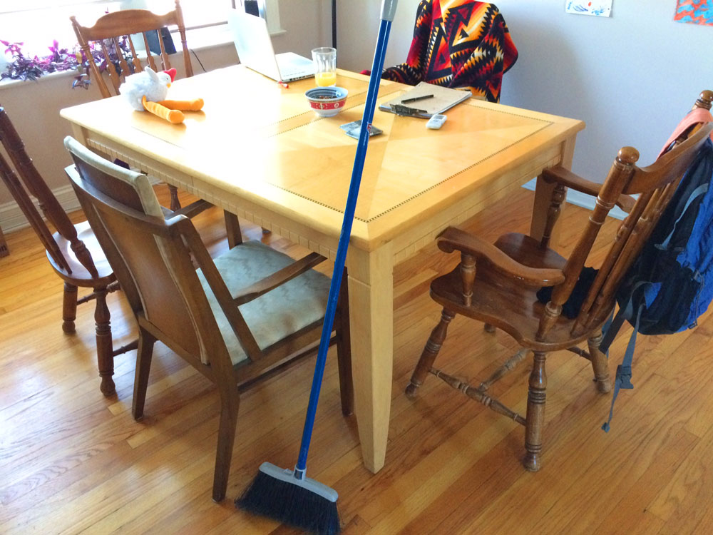 broom leaning against a kitchen table