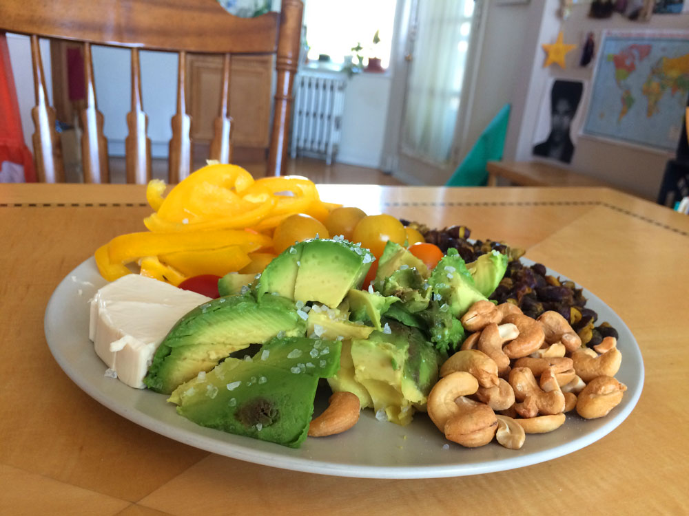 plate on a kitchen table with fresh cheese, sliced yellow peppers and avocado, cashews, sweet grape tomatoes, and black beans