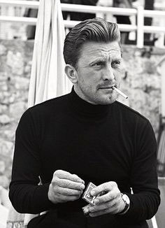 black and white photo of young Kirk Douglas smoking a cigarette and wearing a dope black turtleneck