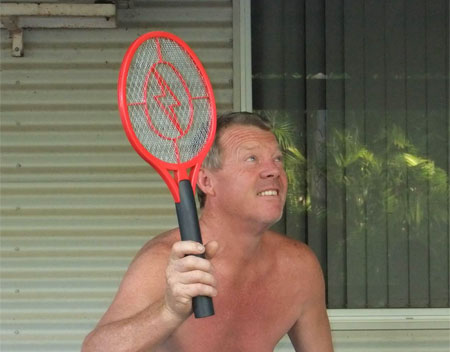photo of a shirtless middleaged sunburned white man with a raquet bug zapper